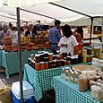 Farmers market vendors with preserves and pickles
