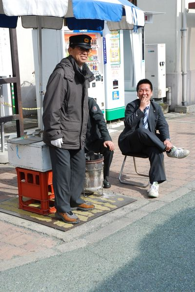 Men keeping warm around coal bucket