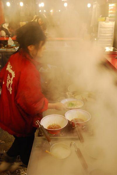 Ramen lady cooking through steam